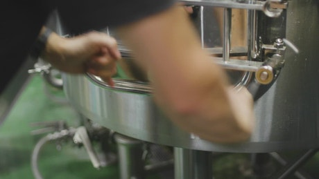 Brewer opening a barley bagasse tank