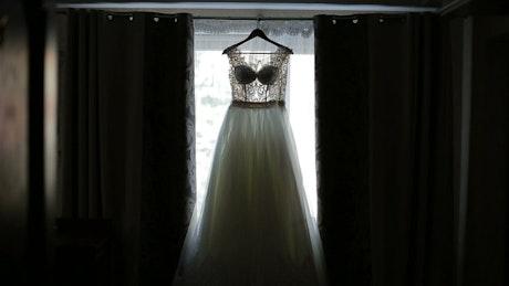 Bride admires wedding dress hanging in window