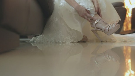 Bride in dress adjusting one of her slippers