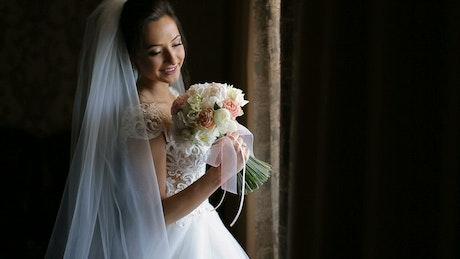Bride in wedding dress holding flower bouquet on black background