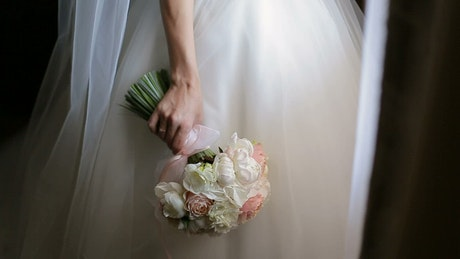 Bride in wedding dress smells bouquet of roses