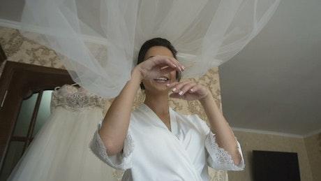 Bride tosses veil while dressing for wedding