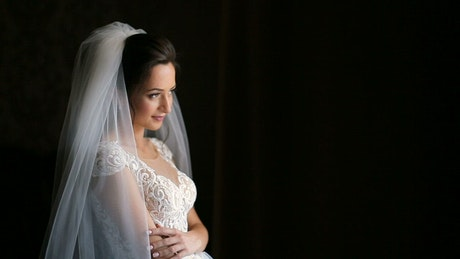 Bride with dark hair smiles and poses on black background