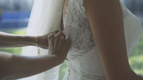 Bridesmaid helping to put on a wedding dress