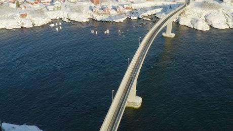 Bridge crossing the sea into snowy village