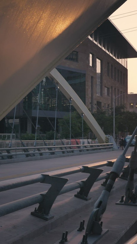 Bridge of cars and people in the city at sunset