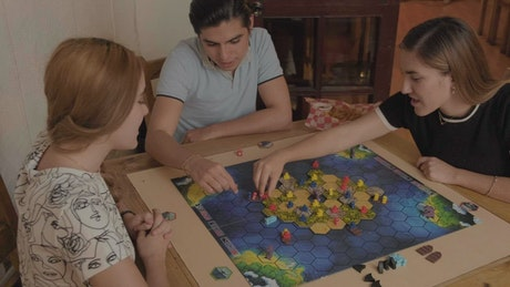 Brothers playing with a board game in a dining room