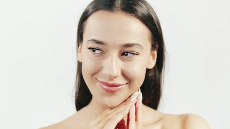 Brunette skincare model smiles on white background