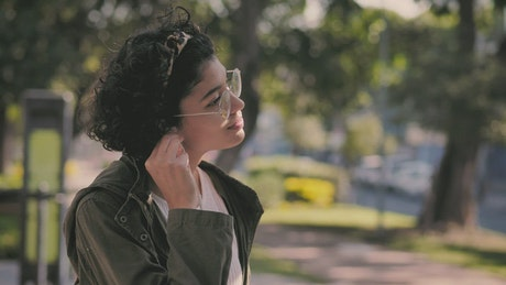 Brunette teen  puts on her headphones and smiles
