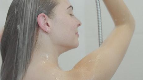 Brunette woman washing hair in shower