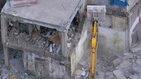 Bulldozer destroying a concrete building