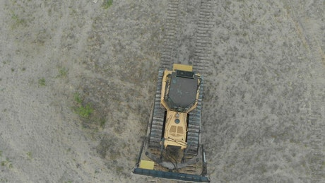 Bulldozer driving through a dirt field
