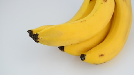 Bunch of bananas rotating in a white space