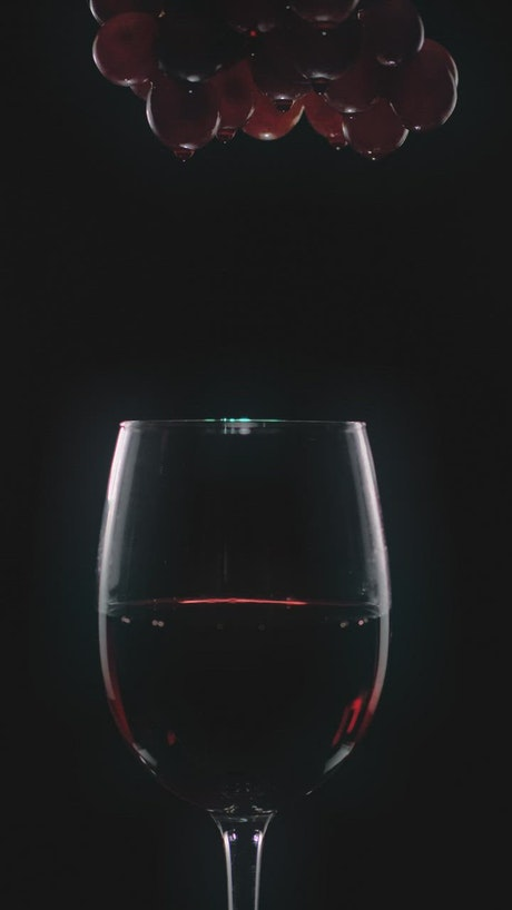 Bunch of grapes dripping wine into a glass
