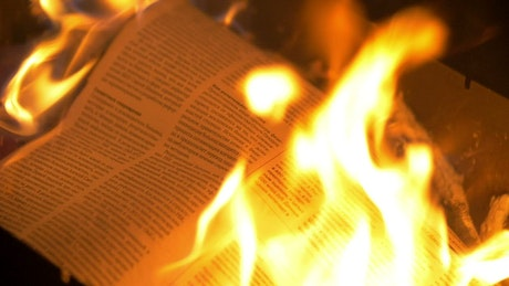 Burning a newspaper in a campfire