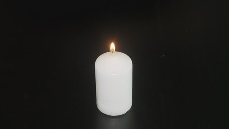 Burning candle against a dark background