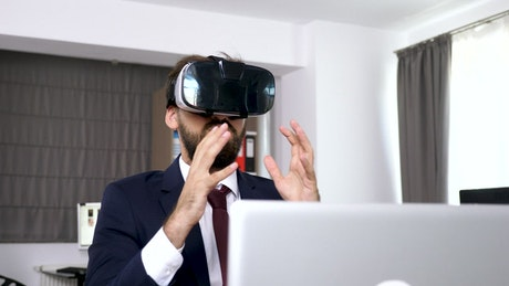Businesman uses VR headset to visualise data