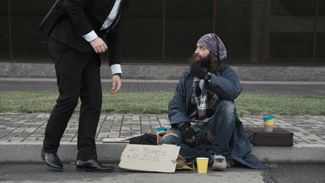 Business man and beggar sitting on the street
