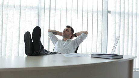 Business man reclines in chair and thinks