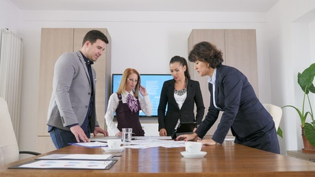 Business team discuss ideas while standing at table