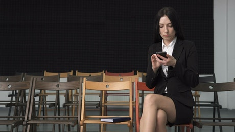 Business woman texting at a empty seminar
