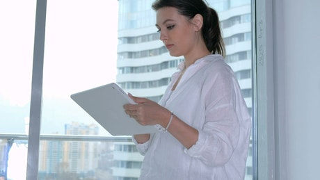 Business woman working on her tablet from home