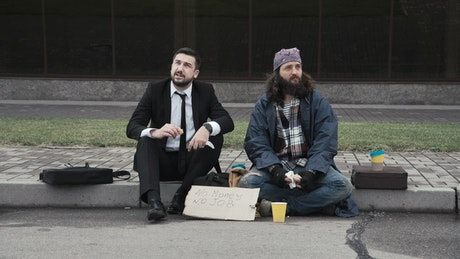 Businessman and homeless sitting on the sidewalk