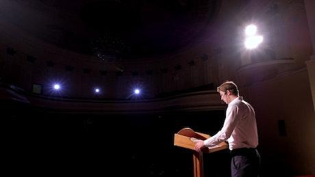 Businessman gives a talk in an auditorium
