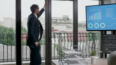 Businessman in suit thinks in front of office windows