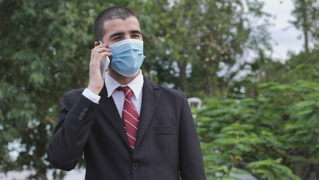 Businessman in suit wearing face mask while talking on the phone