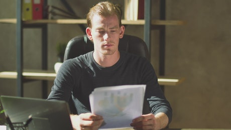 Businessman looks over finance reports and frowns