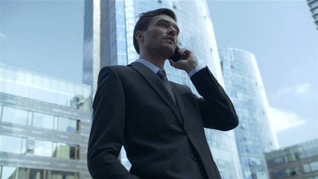 Businessman on the phone in a city