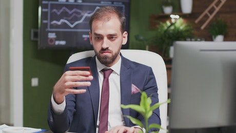 Businessman online shopping in office holds credit card
