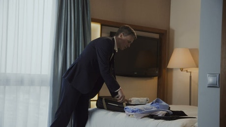 Businessman preparing the luggage in a hotel room