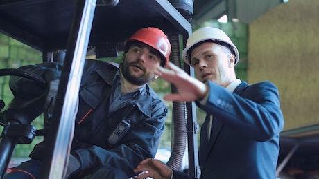Businessman talking to lifting vehicle operator