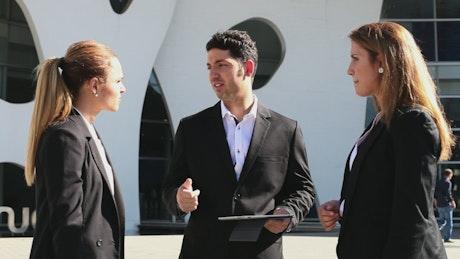 Businessman talking to two businesswomen