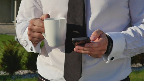 Businessman with coffee mug checking mobile phone