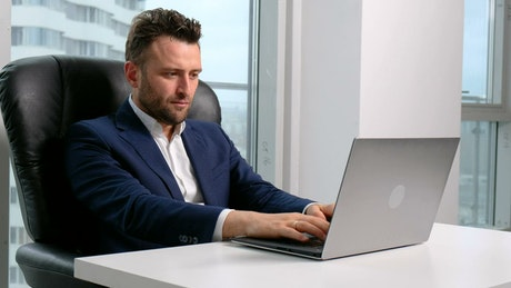 Businessman working on a laptop at his desktop