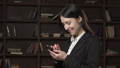 Businesswoman texting in the library