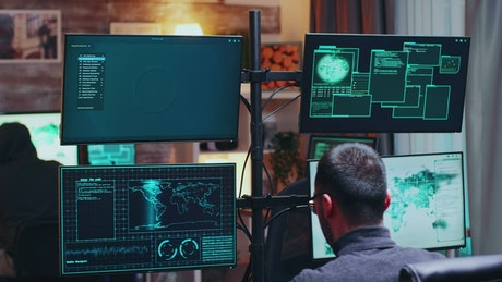 Busy hackers talk between data visualisations on monitors