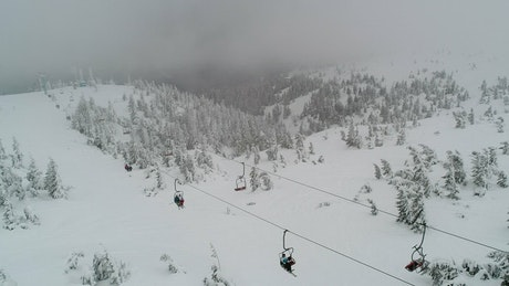 Cable car crossing a snowy and cloudy mountain
