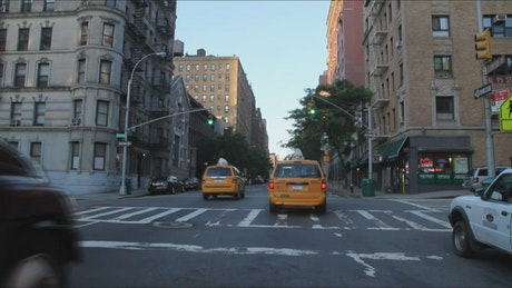 Cabs driving down a street in NYC