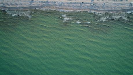 Calm sea reaching the beach, top aerial shot