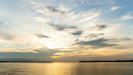 Calm seas below a sunset