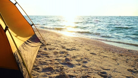 Camping tent on the beach at sunrise