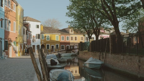 Canal boats docked by colorful houses