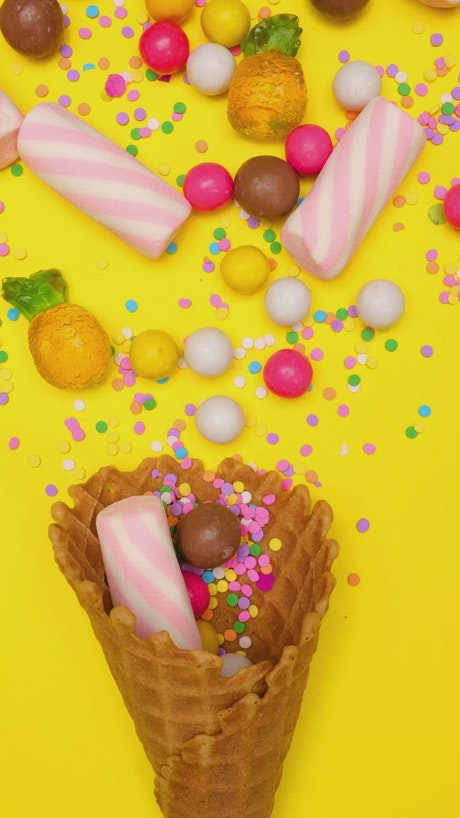 Candies in a waffle cone on a yellow background