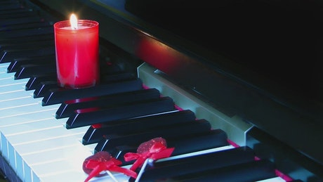 Candle on a piano keyboard
