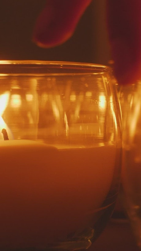 Candles in the dark arranged by a person's hand