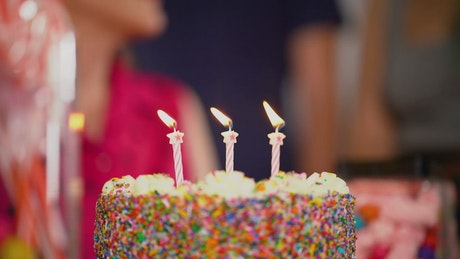 Candles on a cake being extinguished by the celebrated